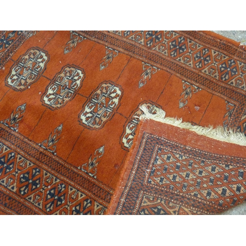 563 - A small Persian Bokhara rug, with five elephant pad motifs on a red ground, 96 x 62cm...