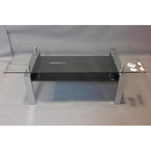 611 - A contemporary chrome and glass low table, with black tempered glass undertier, H.43 W.120 D.60cm...