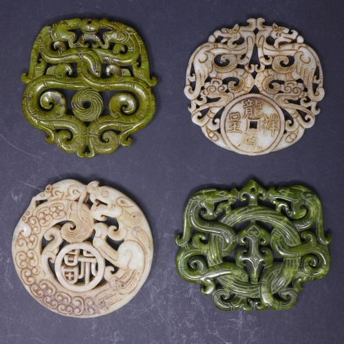 523 - Four Chinese hardstone amulets, with pierced decoration of dragons, Diameter 7cm (largest) (4)...