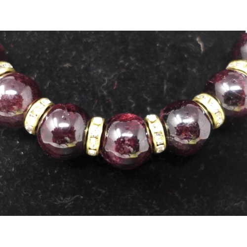 524 - A beaded garnet, gold plated and cubic zirconia set necklace and matching pair of earrings...