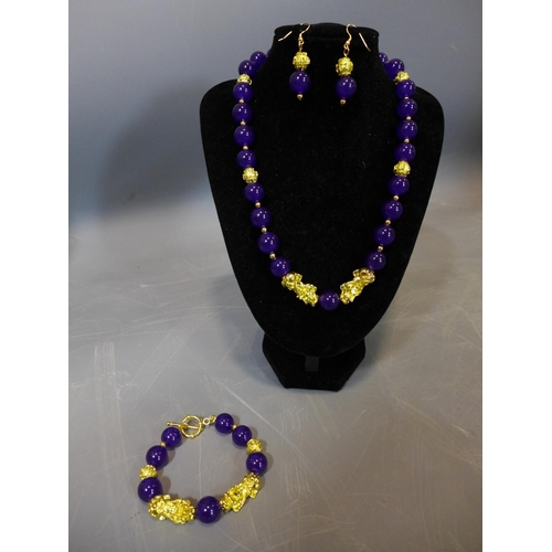 526 - A beaded purple jade and gold plated jewellery suite, to include necklace, bracelet and earrings...