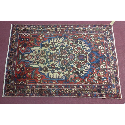 542 - A Central Persian Bakhtiari rug, repeating stylised floral motifs on an ivory field, within stylised...