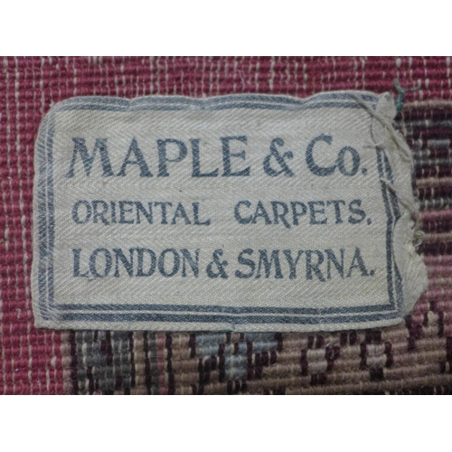 564 - A large early 20th century Persian design carpet, with label for Maple & Co. London, central floral ...