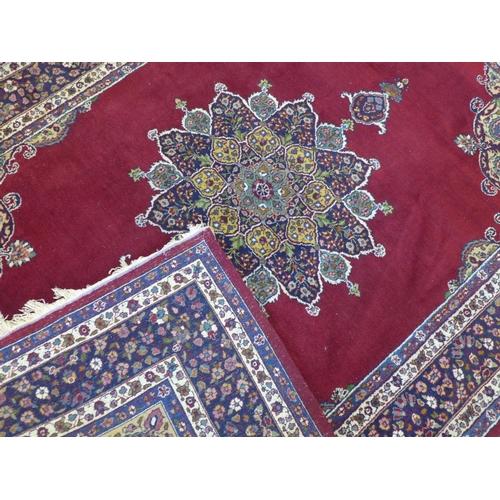 577 - An antique Persian Kirman rug of Safavi design, central floral medallion and floral spandrels on a m...
