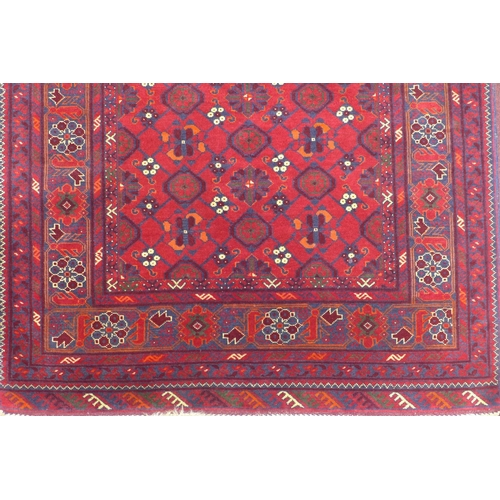578 - An antique Afghan Bashir rug, repeating petal motifs on a red ground, within stylised floral border ...