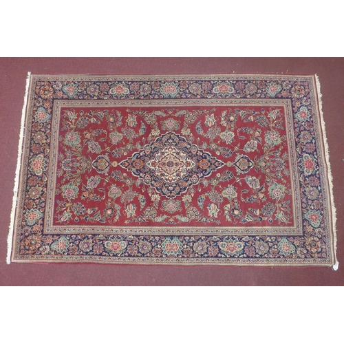 579 - An antique Persian Kashan rug, central floral medallion with floral motifs on a maroon ground, conta...