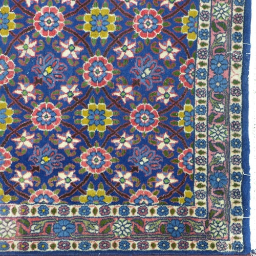 583 - A Persian Tehran rug, floral motifs on a blue ground, within floral border, 146 x 96cm