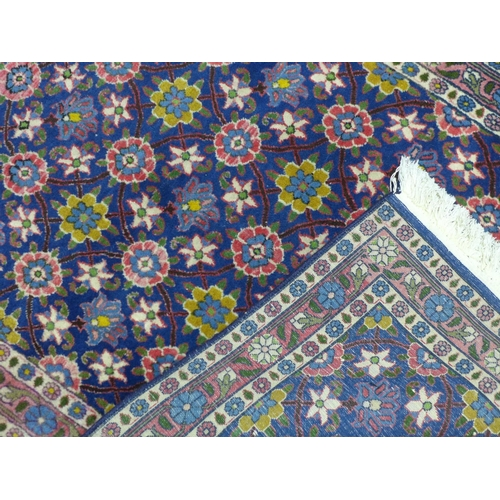 583 - A Persian Tehran rug, floral motifs on a blue ground, within floral border, 146 x 96cm...