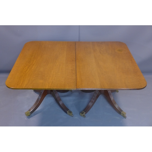 22 - A Regency mahogany extending dining table, with two extra leaves, on turned supports on quadri-form ...