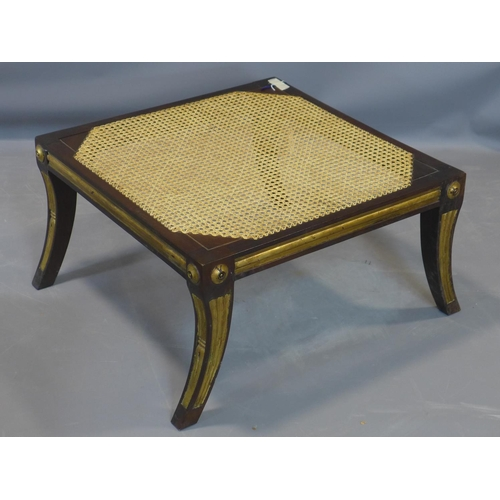 32 - A Regency style footstool in the manner of William Kent, with caned seat, having gilt detailing, rai...