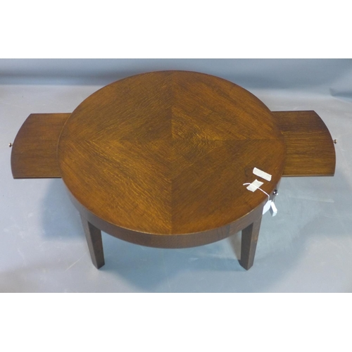 69 - A circular oak side table, with quarter veneered top, having two brush slides, on square tapered leg...