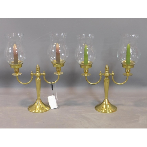 218 - A pair of two branch candelabras, with glass shades, raised on spreading circular base, H.40cm...