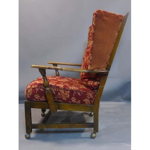 27 - An oak winged back armchair, with floral upholstered cushions, raised on square legs and castors, H....