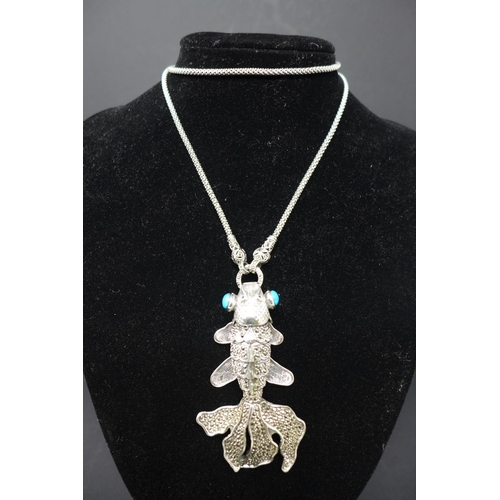 206 - A white metal pendant necklace modelled as a fish with turquoise eyes, L.8cm (pendant)...