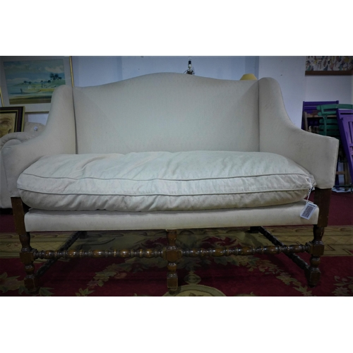 37 - An early 20th century settee, with cream upholstery, on turned supports joined by stretchers, H.99 W...