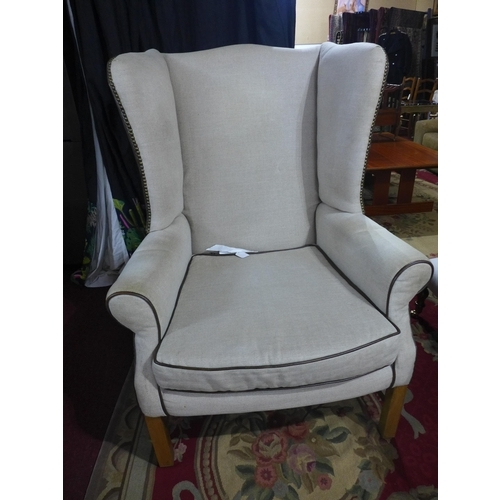 38 - A pair of wingback armchairs, with linen and stud bound leather upholstery, on square legs...
