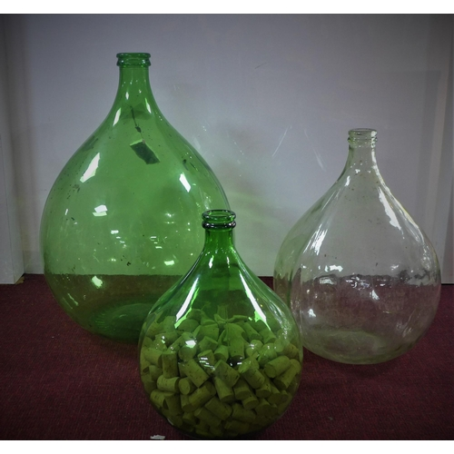 175 - Three large glass bottles/carboys, one filled with corks, H.67cm (largest)...