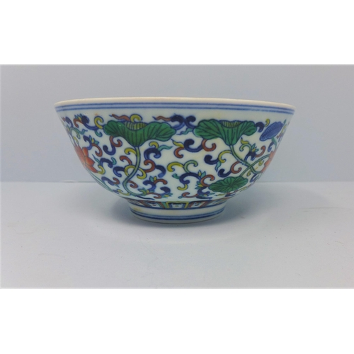 133 - A Chinese doucai bowl, decorated with scrolling foliage, bearing six character marks within two blue...