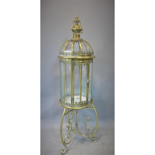 223 - A contemporary gilt metal storm lantern, on stand with three scrolling feet, H.109cm...