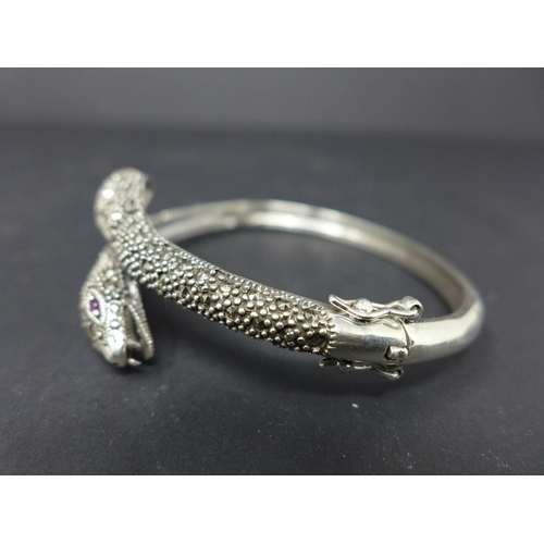 185 - A white metal and marcasite snake bangle with ruby eyes...