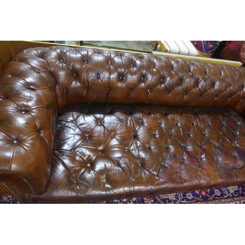 206 - A Victorian brown leather button back and stud bound Chesterfield Sofa, raised on turned legs, H.66 ...