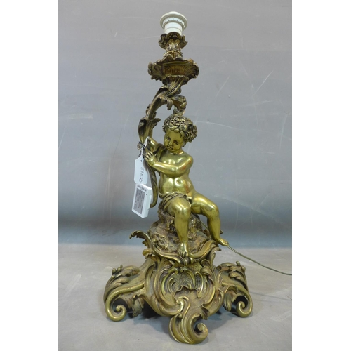 185 - A large gilt bronze figural table lamp, in the Roccoco style, with cherub seated on elaborate C-scro...