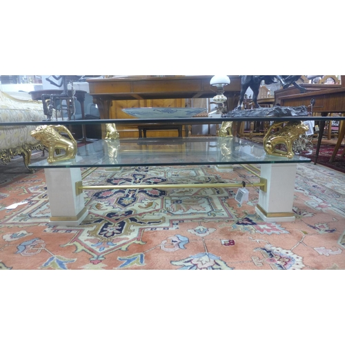 578 - A two tier glass coffee table, with painted wooden supports with gilt brass lion stands, H.40 W.130 ...