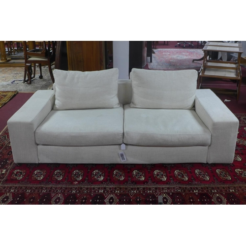 584 - A contemporary two seater sofa with cream upholstery, with four cushions, H.60 L.202 D.98cm...