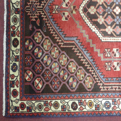 624 - A North West Persian Zanjan rug, double pole medallion with four corner medallion on a rouge field, ...