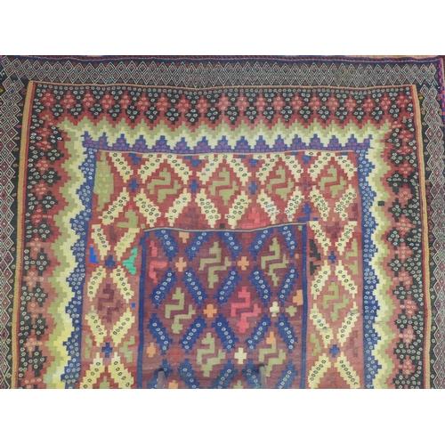 628 - A North East Persian Sumak kelim, repeating stylised geometric motifs on a terracotta field, guarded...