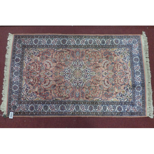 633 - A pure silk Persian Kirman rug, central floral medallion with stylised motifs on a pink ground, with...