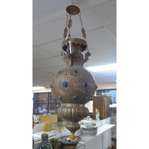 702 - A Moroccan Mamounia copper ceiling pendant light, with pierced scroling decoration and coloured glas...
