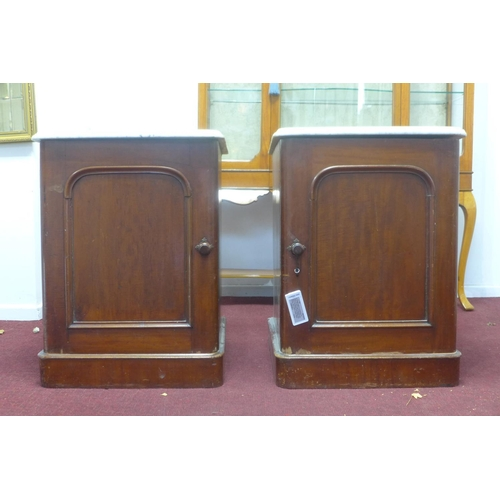 729 - A pair of late 19th / early 20th century mahogany pot stands, with marble tops above cupboard doors,...