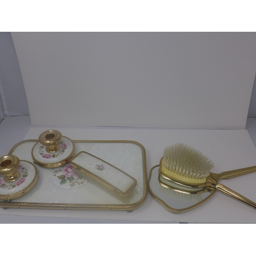 521 - A vanity set, comprising hand mirror, hair brush and clothes brush, a mounted comb, a tray and two c...