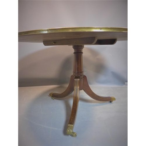 547 - An exotic hardwood and brass mounted circular centre table, with green leather skiver with brass rim...