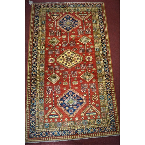 568 - A Russian Kazakh rug, three central diamond medallions and geometric motifs on a rouge field, within...