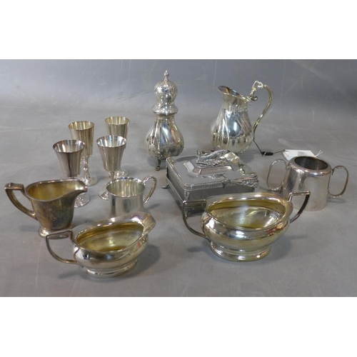 110 - A collection of silver plated items including four schnapps glasses, two milk jugs, two sugar bowls,...