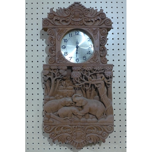 186 - A Southeast Asian clock, the elaborately carved case with elephants and scrolling foliage, quartz mo...