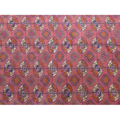 1 - A Turkoman carpet with repeating gul motifs on a red ground, within geometric border and bands, frin...