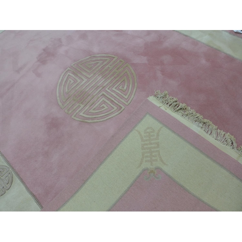 2 - A pink ground Peking Chinese carpet, with central Chinese symbol on a pink ground, within a cream bo...