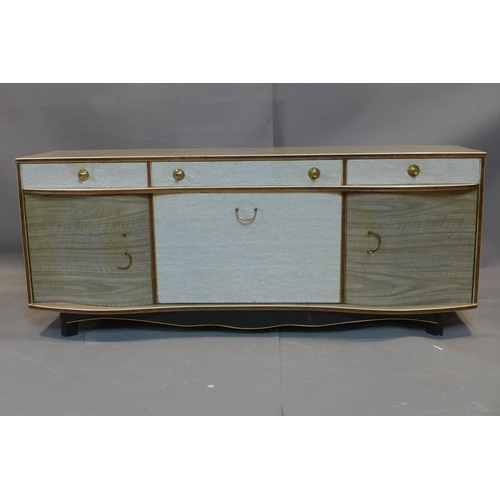 12 - A 1960's serpentine fronted sideboard, with one long and two short drawers, above central drinks cup...
