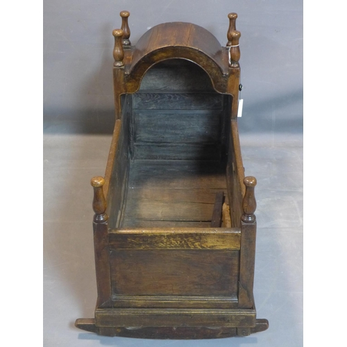 23 - An 18th century oak  cradle, with turned finials and panelled sides, H.75 W.104 D.60cm...