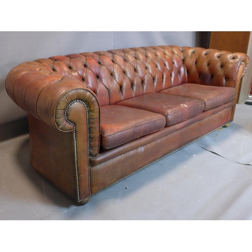26 - A three seater leather Chesterfield sofa, with button back upholstery, heavily worn, H70cm, W210cm, ...