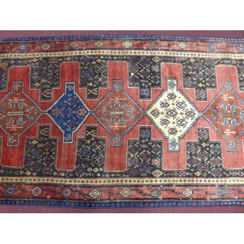 68 - A north west Persian senneh Rug, 275cm x 115cm, repeated sapphire diamond medallions, with repeat pe...