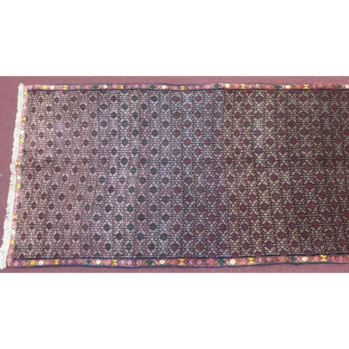71 - A north west Senneh runner 365cm x 90cm, repeated patterns on a sapphire field, and floral borders...