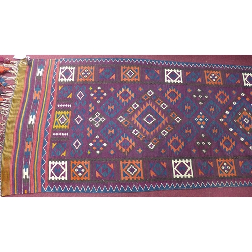 72 - An Afghan Belouch kelim, with three diamond medallions and geometric motifs on a purple ground, 142 ...