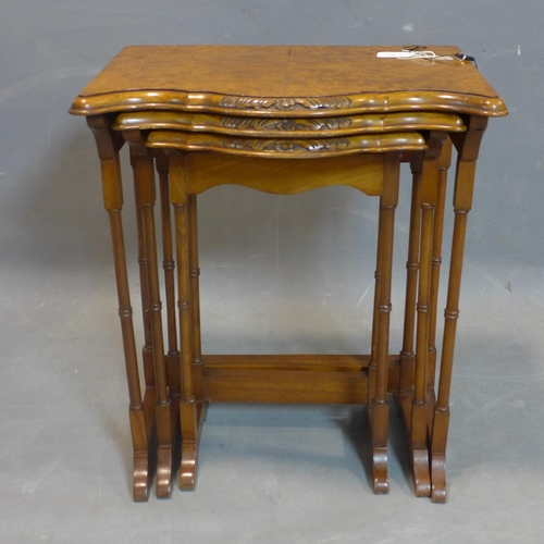 77 - A walnut nest of three tables, with quarter veneered tops with serpentine fronts, raised on slender ...