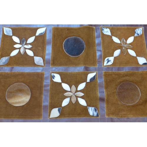 83 - A leather and cow hide rug, with squares of repeating geometric patterns, 174 x 105cm...