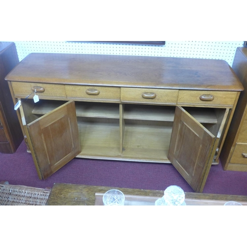 84 - A mid 20th century Ercol teak sideboard, with four short drawers and two pairs of double doors, on c...