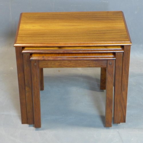 122 - A nest of three Danish exotic hardwood tables, marked 'Made in Denmark' to bases, H.46 W.54 D.39cm...